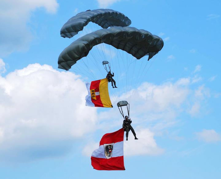 Zwei Fallschirmspringer mit schwarzen Schirmen und der Österreich Flagge
