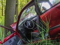 Rotes Auto liegt im Graben mit der Schnauze an einem Baum
